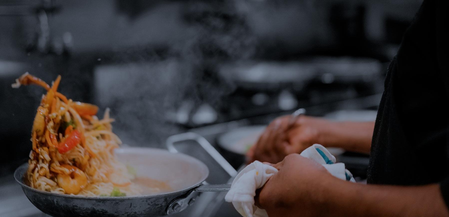 Un cuisiner qui fait cuire des pâtes dans une casserole.