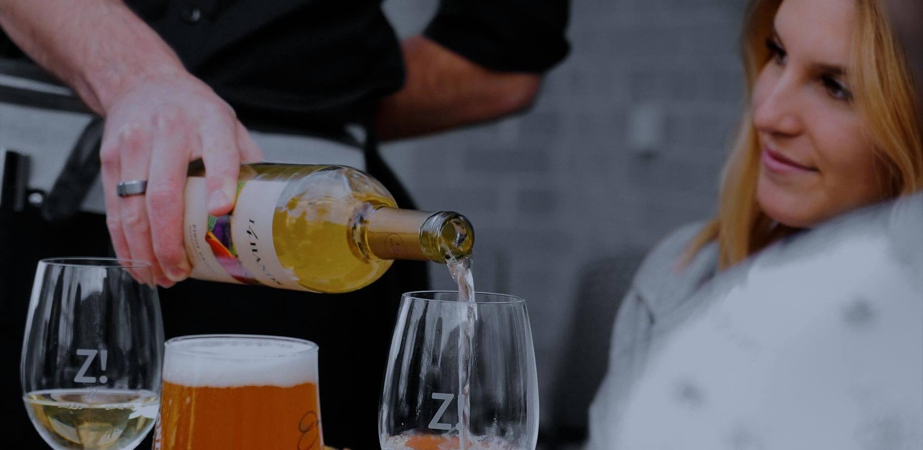 Un serveur qui verse du vin à une cliente.