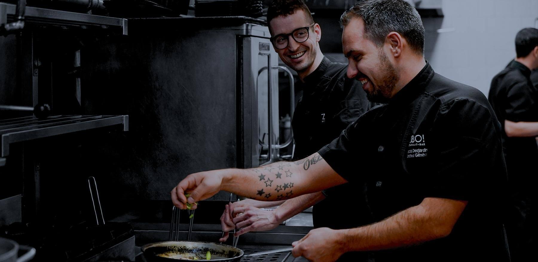 Deux cuisiniers qui préparent un plat.